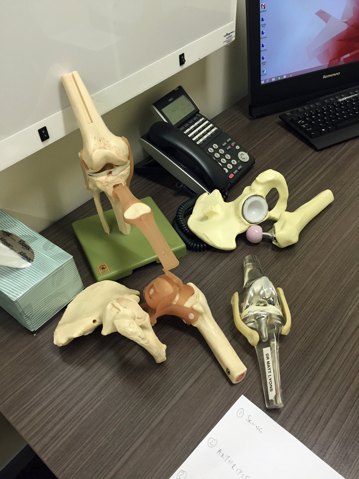 The cluttered paraphernalia on an orthopaedic surgeon's desk. My list of questions is also in the photograph.